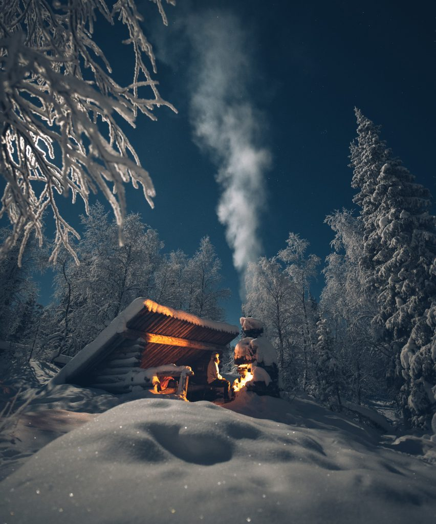 Hiker enjoying the glow of a bonfire at a wintry lean-to. The Laavu room is inspired by age-old lean-tos built in the wilderness.