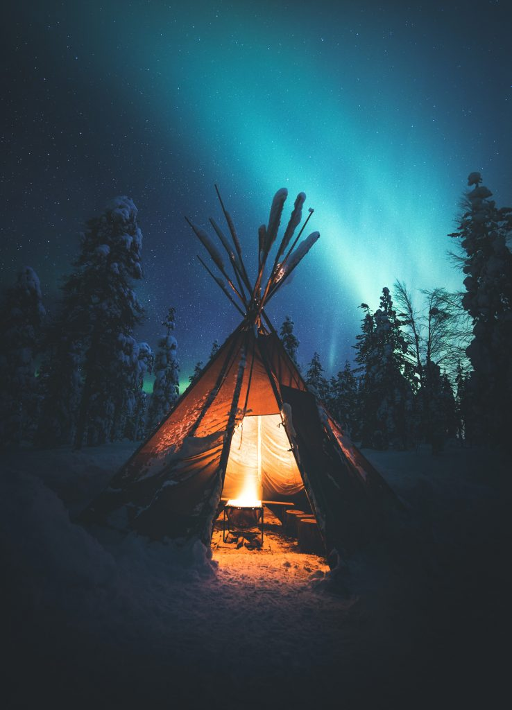 A bonfire in a goahti under the Northern Lights. The Kota room is inspired by traditional goahti tents. Image: Jani Ylinampa